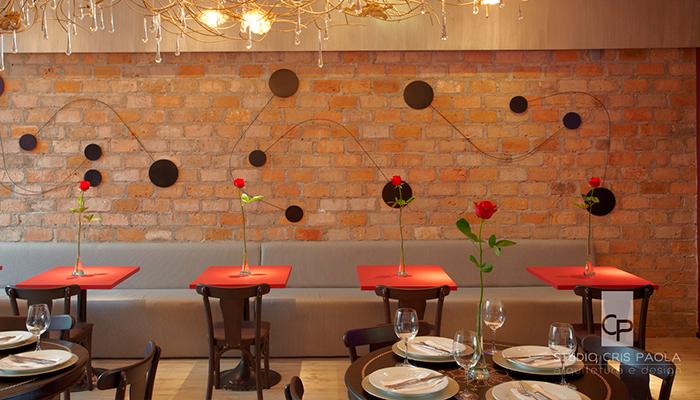 restaurante com parede  de tijolinhos e mesas vermelhas
