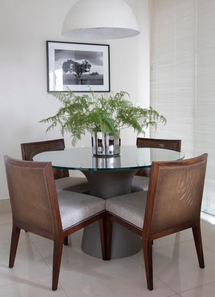 Sala de almoço branca, mesa de madeira e persiana plissada.