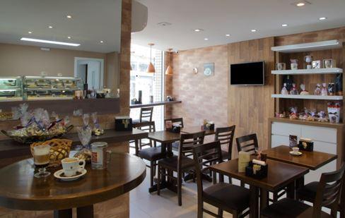 cafeteria com parede de tijolinho e móveis escuros