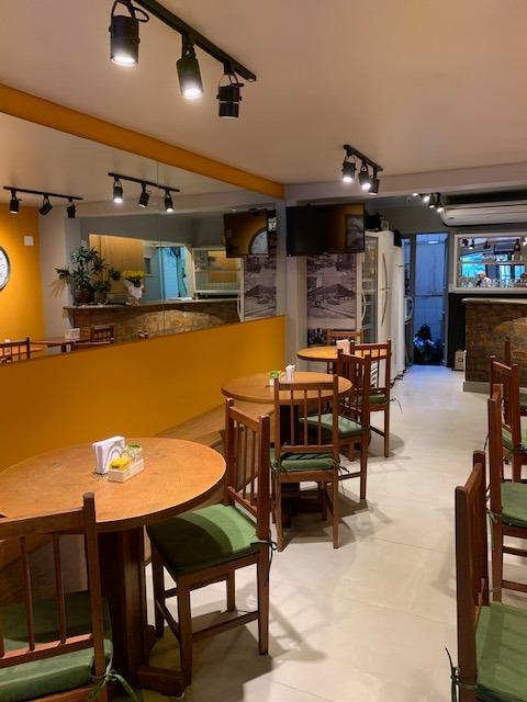 cafeteria com parede amarela e espelhos