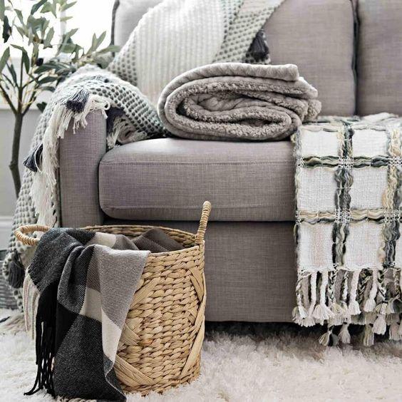 várias mantas de tecidos diferentes no sofá