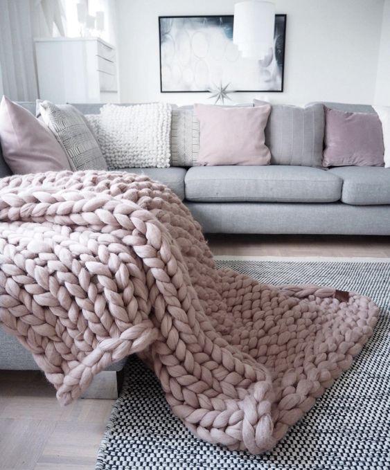 maxi tricot rosa em cima do sofá cinza