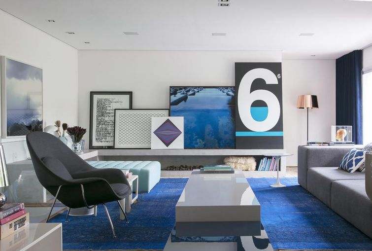 sala de estar com cores em azul e quadros na prateleira
