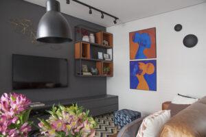Sala de TV com parede preta e nichos em serralheria