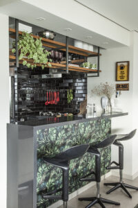 Cozinha com estante em serralheria e detalhes em preto e verde