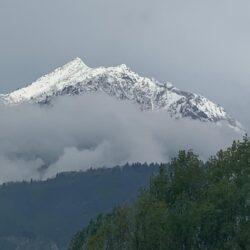 montanha com neve ao fundo e paisagem verde