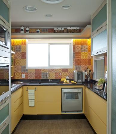 Cozinha com marcenaria amarela e azulejos coloridas