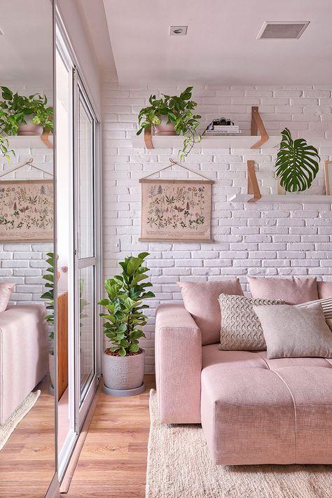Sala estar de parede de tijolinho com sofá rosa e muitas plantas